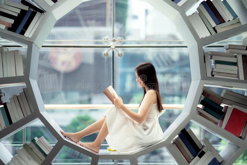 Asian girl student read a text book in library in her University stock image