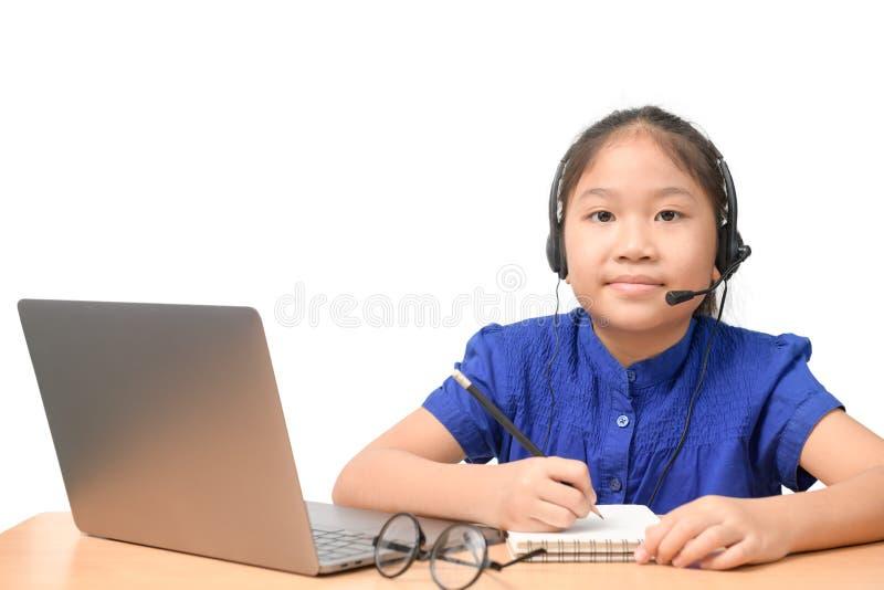 Asian girl student wear wireless headphone study online at home 免版税图库摄影