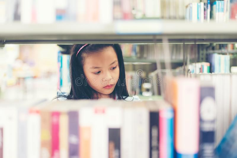 Asian girl student women finding book for reading in library. stock image