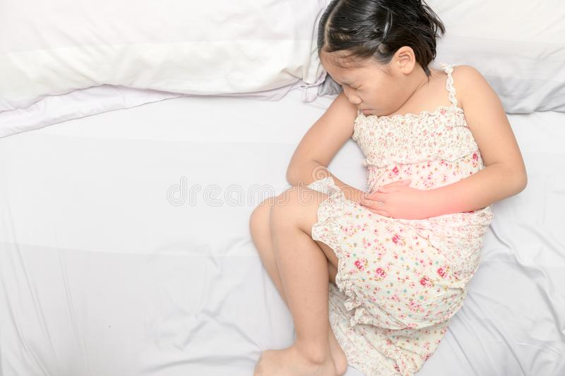 Asian girl suffering from stomachache royalty free stock photo