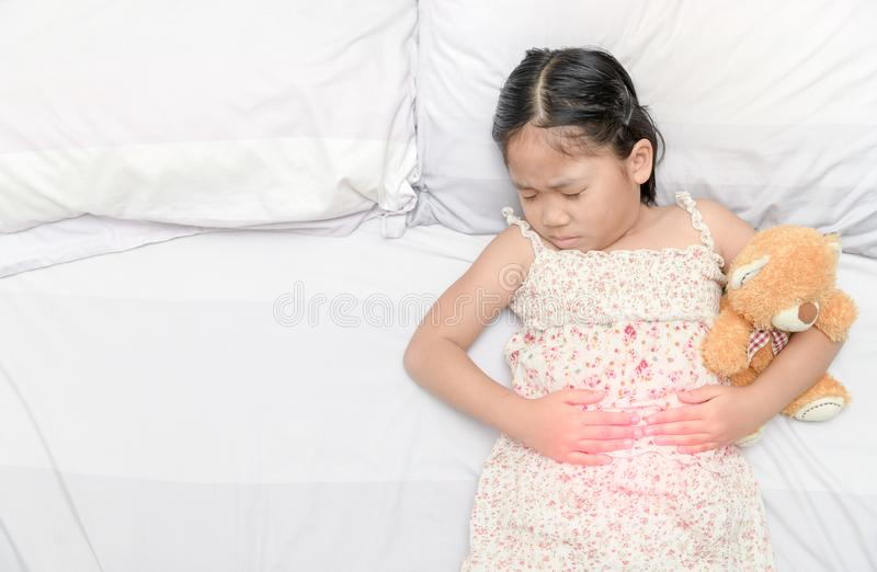 Asian girl suffering from stomachache. And red spot indicating location of pain. healthy concept stock image