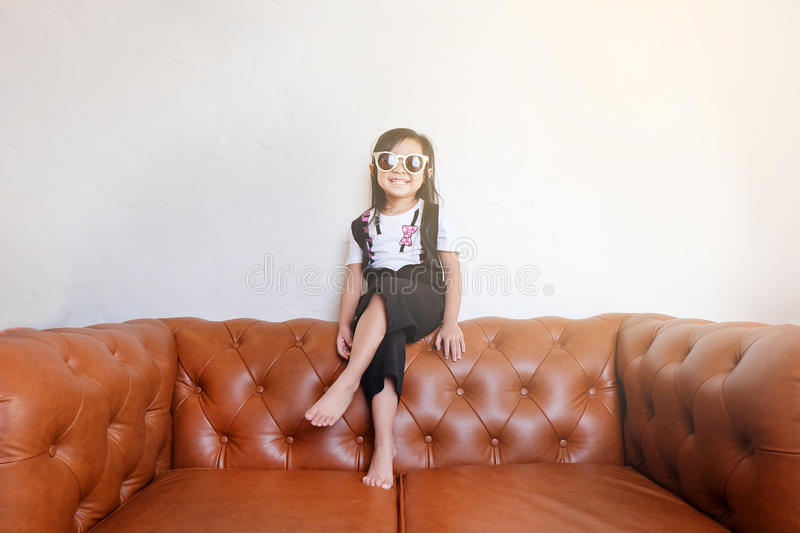 Asian girl with sunglasses sitting on a leather sofa stock photos