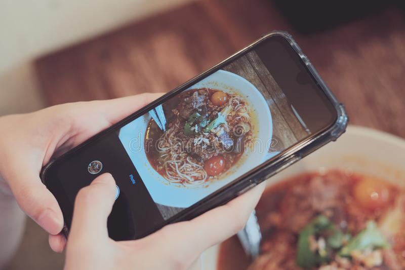Asian girl taking food photo by  her smartphone camera stock photography