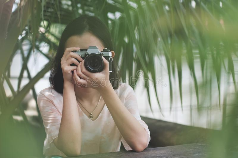 Asian girl taking photo by  SLR Film camera. Woman, black, portrait, fashionable, picture, pretty, female, person, fun, photography, happy, young, beautiful stock photography