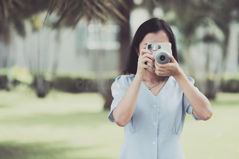 Asian girl taking some photo by instant digital camera stock photo