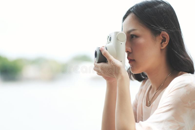 Asian girl taking some photo by instant digital camera stock image