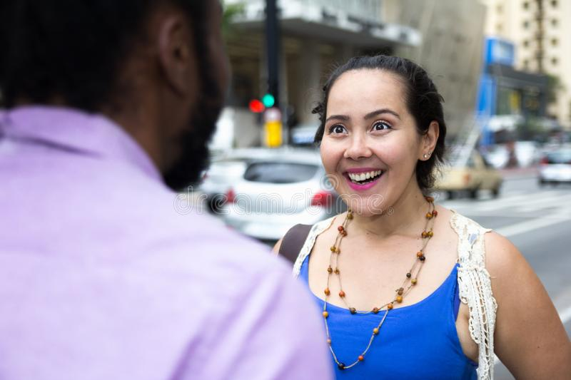 Asian girl talking to african american friend in the streets stock photos