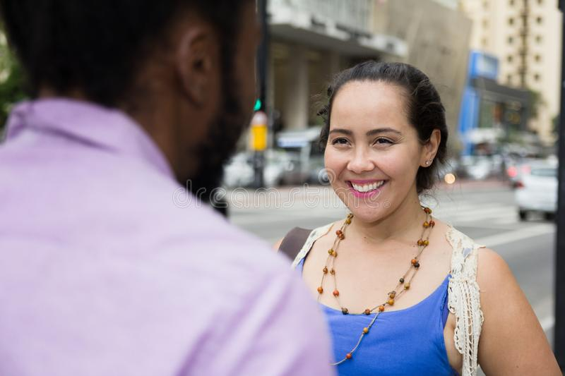 Asian girl talking to african american friend in the streets royalty free stock photo