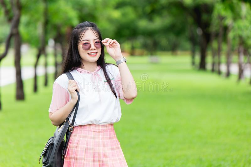 Asian girl teen cute with UV sunglasses brace teeth smiling at green park background stock photography
