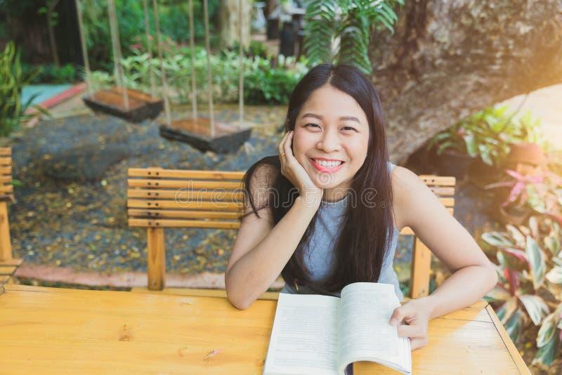 Asian girl teen smile enjoy reading book stock photo