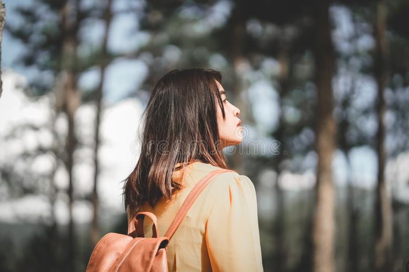Asian girl traveler in yellow dress with backpack walking in the forest. royalty free stock images