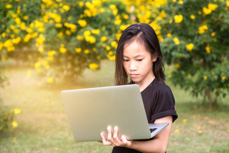 Asian little child girl is using a laptop computer in the outdoor park , internet and education concept royalty free stock photo