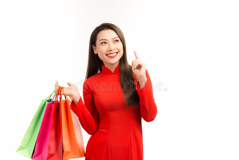 Asian girl in vietnamese ao dai dress with shopping bag isolated on white background.  stock photos