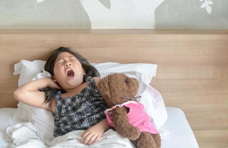 Asian girl wakes up and stretching on bed royalty free stock photo