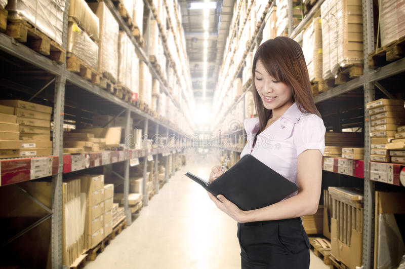 Asian girl in warehouse. Asian girl stock counting in warehouse royalty free stock photos