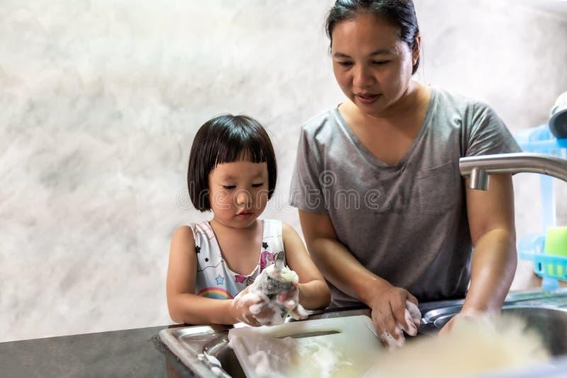 Girl and mom wasing dish, housework stock photos