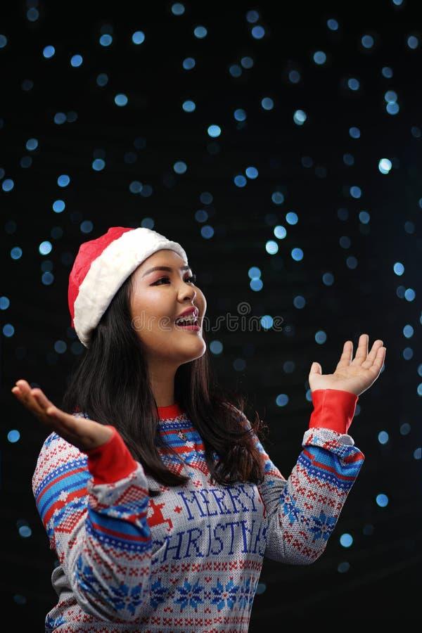 Asian Girl Wearing Christmas Sweater Dark Glow Snow Background. royalty free stock image