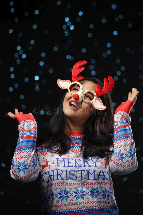 Asian Girl Wearing Christmas Sweater and Christmas Reindeer Glasses Red Nose. Enjoy Glowing Snow stock image