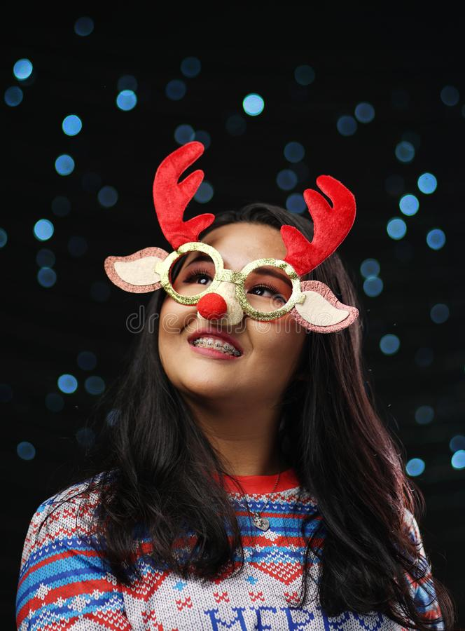 Asian Girl Wearing Christmas Sweater and Christmas Reindeer Glasses Red Nose. Looking Up stock photo