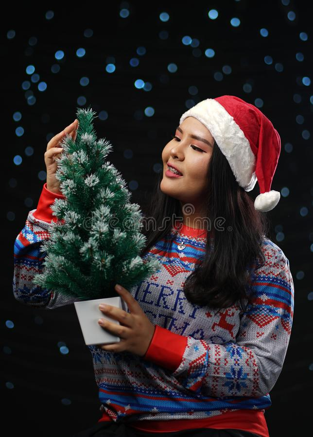 Asian Girl Wearing Christmas Sweater and Santa Hat Holding Small royalty free stock photo