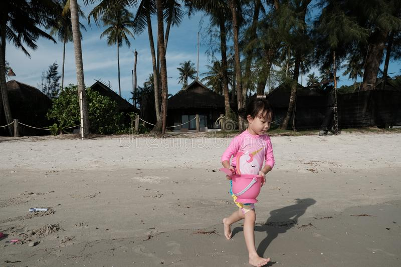 An Asian girl wearing a pink swimsuit is running with a sand bucket at a beach royalty free stock image