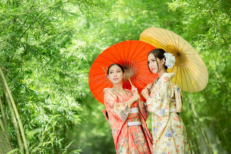 Asian girl wears a kimono and holds a traditional Japanese umbrella. royalty free stock image