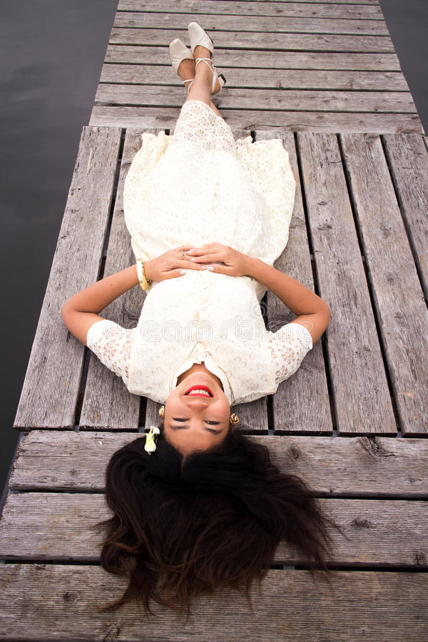 Asian Girl in a White Dress Lying on a Dock royalty free stock photo