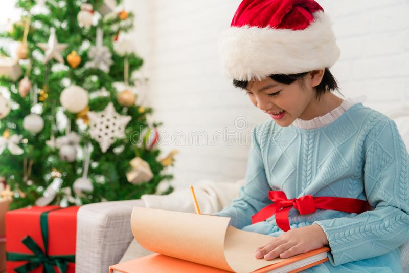 Asian girl writes the letter to santa claus stock photo image of cute asian daughter girl writes the letter to santa claus sitting on sofa at home merry christmas and happy holidays spiritdancerdesigns Gallery