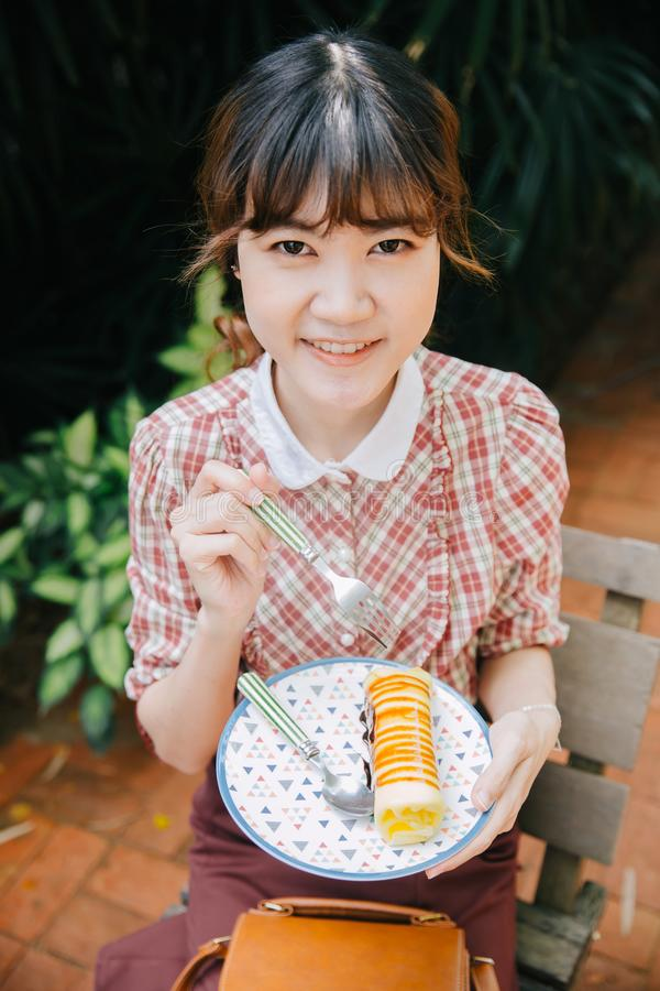 Asian Girl young teen hipster happy eating dessert cake roll stock photo