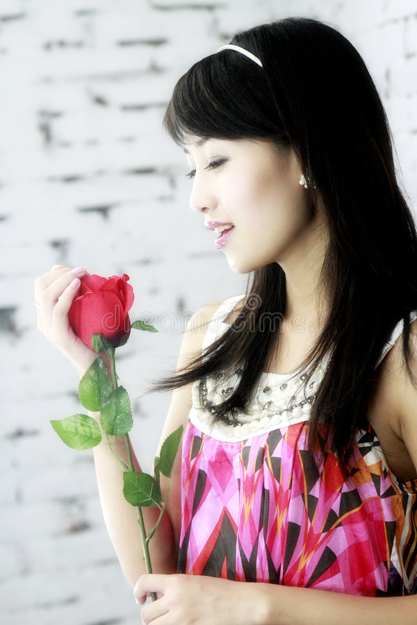 Asian girls and roses. A beautiful Asian girls and roses royalty free stock photography