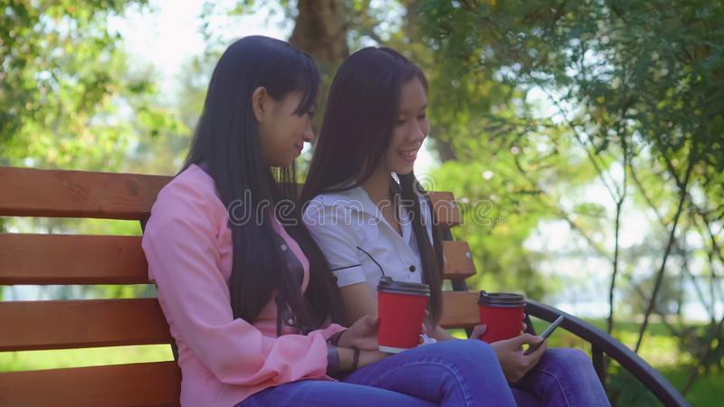 Friends resting in the park sunny day. Asian girls watching funny video on smartphone using application. Women sitting on bench outdoors. Holding paper cups and stock photo