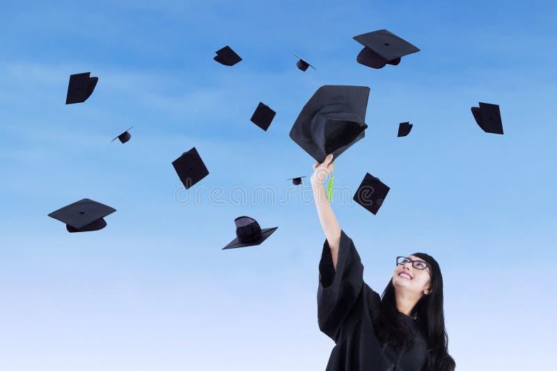 Asian graduate throw graduation cap in air. Asian graduate throw graduation cap under blue sky royalty free stock photo