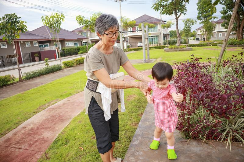 Asian grandmother with granddaughter while playing in the park stock photo