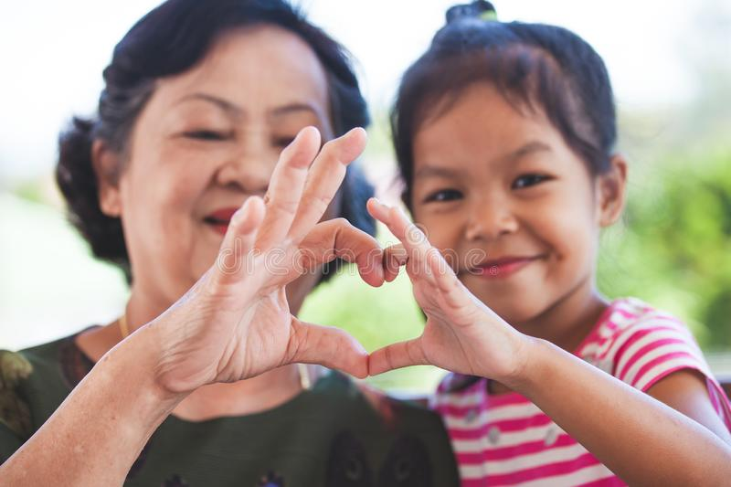 Asian grandmother and little child girl making heart shape with hands together. With love stock photos
