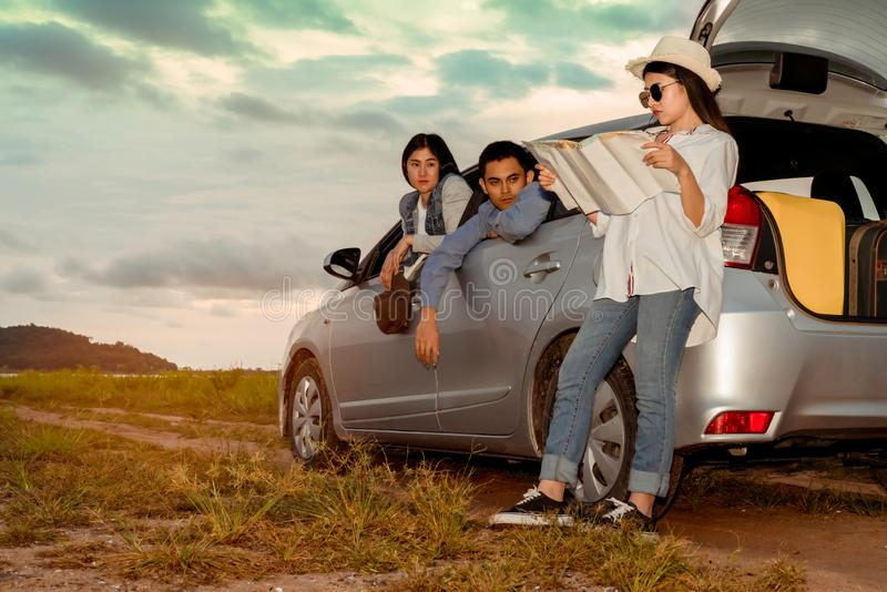 Asian group of friends car travel driving they lost looking maps royalty free stock images