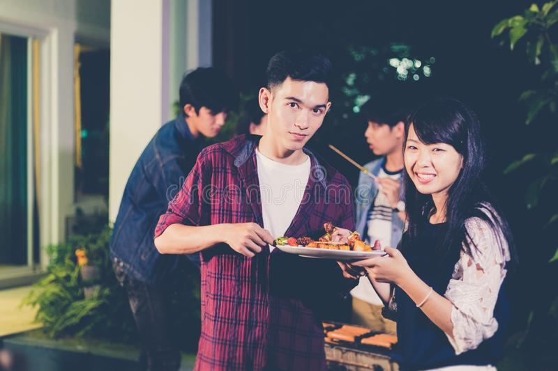 Asian group of friends having outdoor garden barbecue laughing with alcoholic beer drinks on night stock image