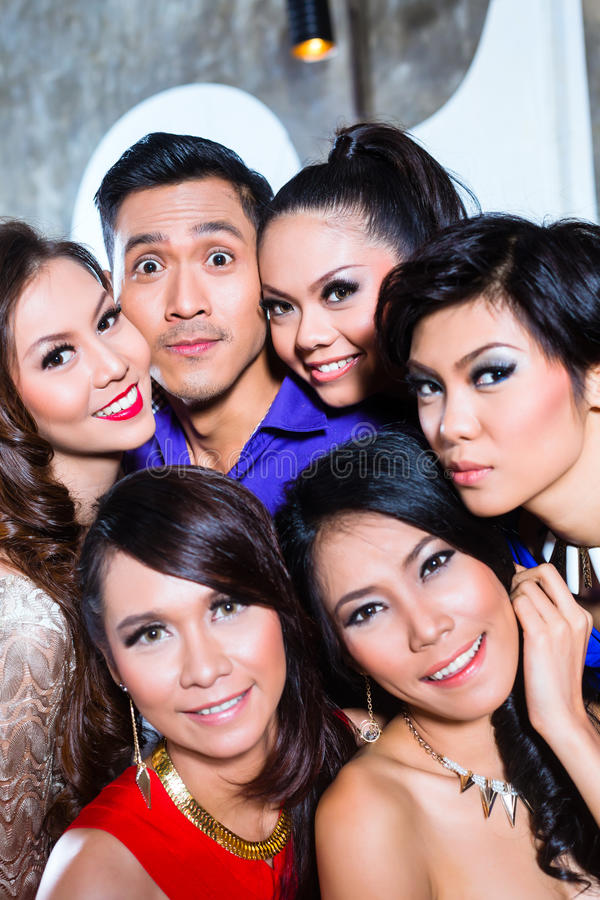 Asian group of party people taking pictures fancy night club royalty free stock photography