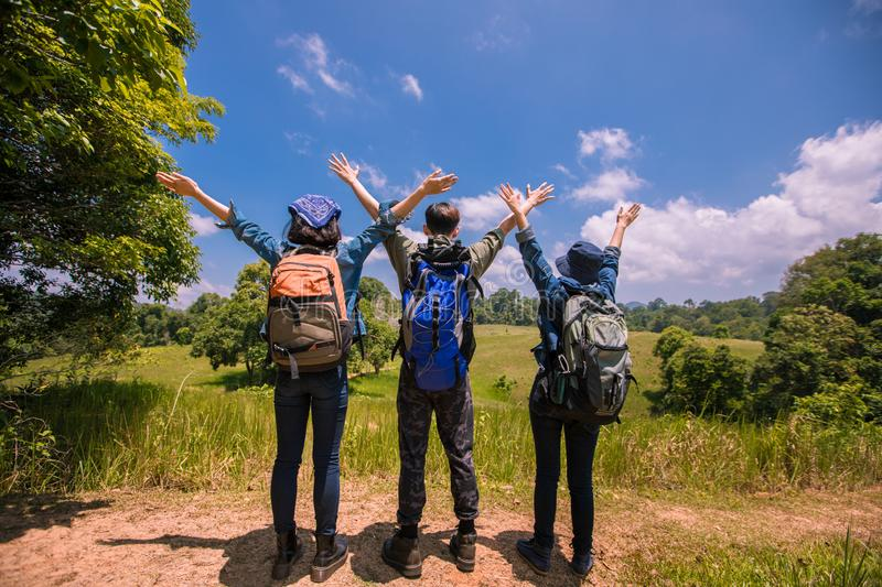 Asian Group of young people with friends backpacks walking together and happy friends are raised arms and enjoying a beautiful stock images