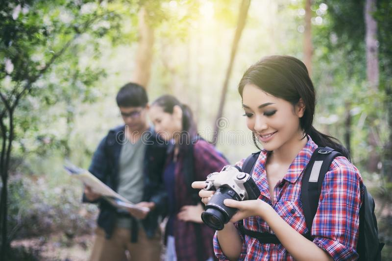 Asian Group of young people Hiking with friends backpacks walking together and looking map and taking photo camera by the road royalty free stock images