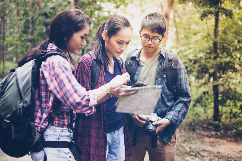 Asian Group of young people Hiking with friends backpacks walking together and looking map and taking photo camera by the road. And looking happy ,Relax time on royalty free stock photo