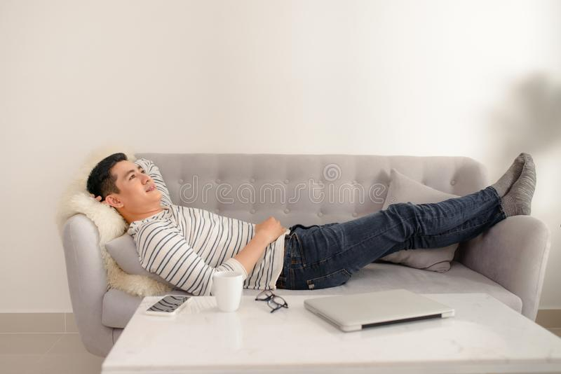 Asian guy daydreaming and rest at home. Asian man relaxed and sleep on sofa indoor. Handsome male model royalty free stock images