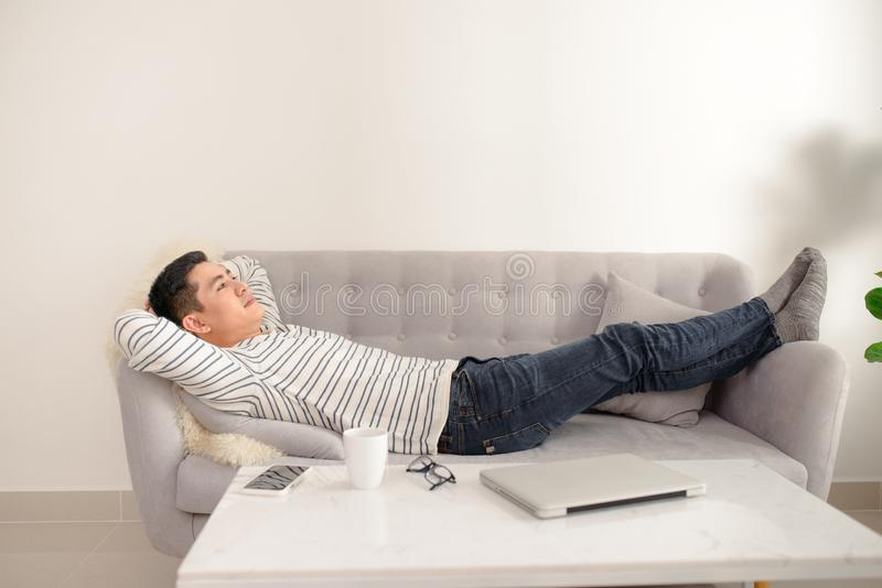 Asian guy daydreaming and rest at home. Asian man relaxed and sleep on sofa indoor. Handsome male model. stock photography