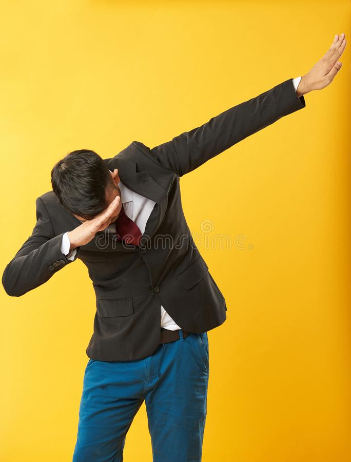 Asian guy doing dab. On yellow color background royalty free stock photo