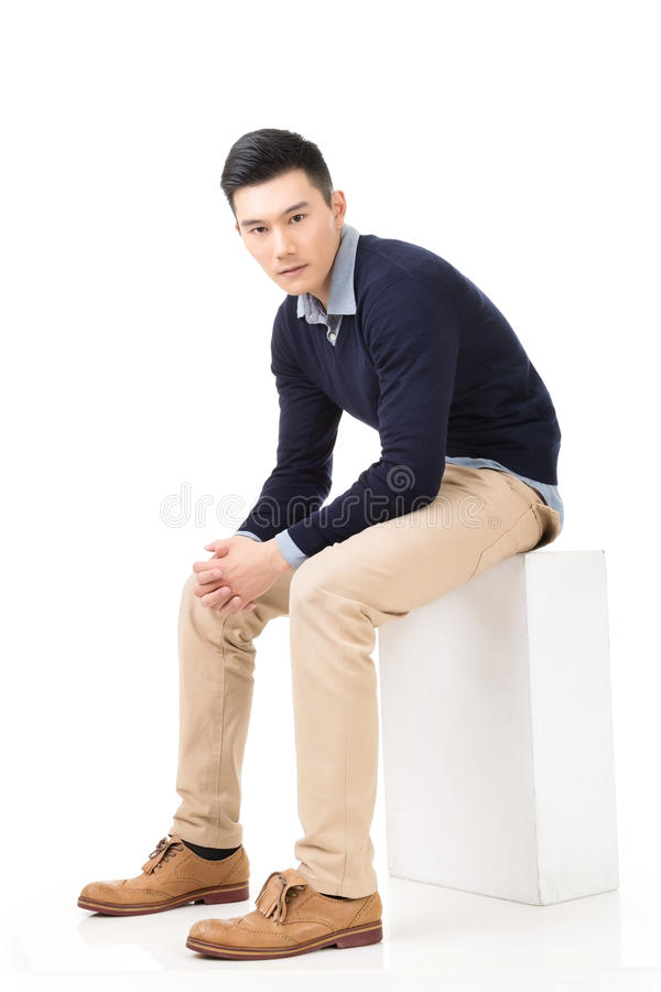 Asian guy sit. Handsome Asian guy sit pose, full length portrait isolated on white background stock photos