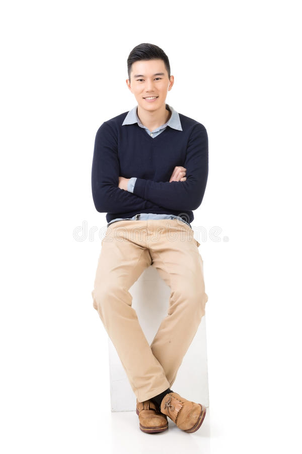 Asian guy sit. Handsome Asian guy sit pose, full length portrait isolated on white background royalty free stock images