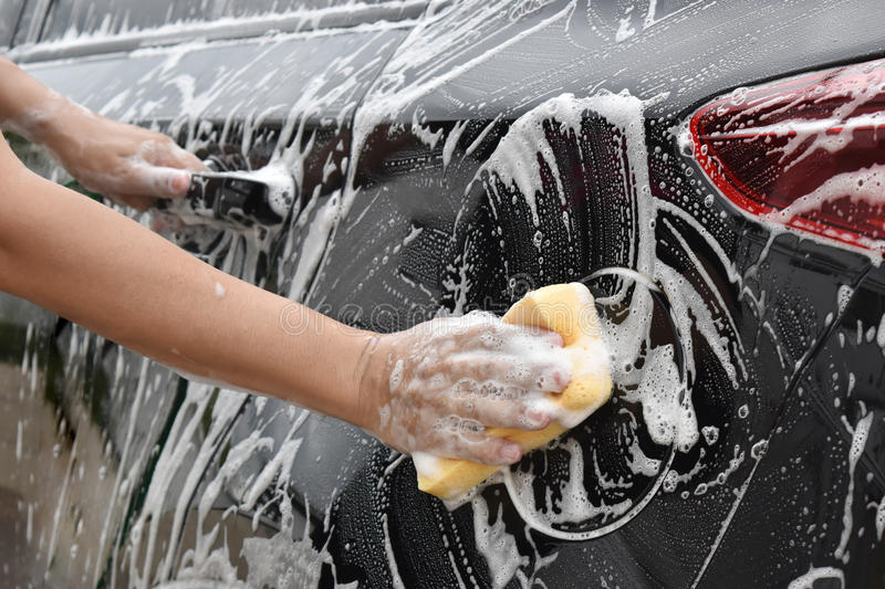 Asian hand holds sponge with car wash To clear the sides of the. Black car stock photography