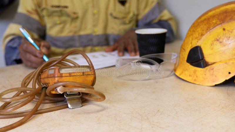 Asian hand written Job Hazard Analysis JHSrisk assessment on the table when working on confined restricted space with gas tester. Defocused isolated construction royalty free stock photo