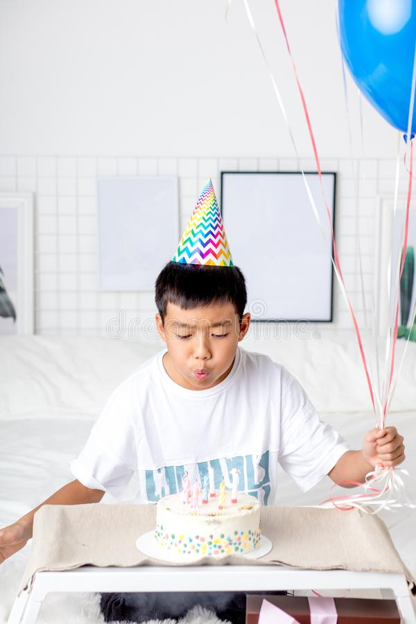 Asian handsome boy blowing out candles from the cake stock photography