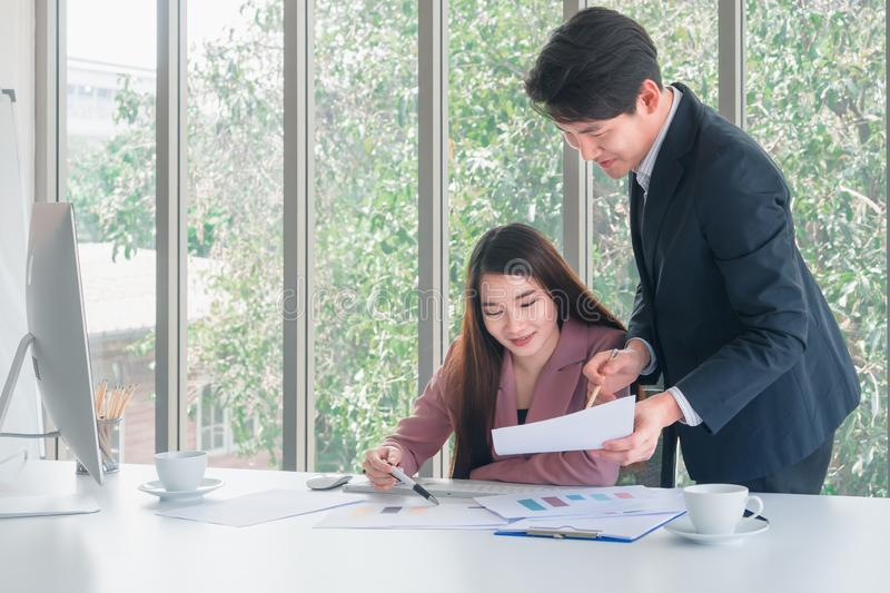 Asian handsome businessman in navy blue suit stand to explain job details to long hair beautiful business woman in pink suit sit a royalty free stock photo