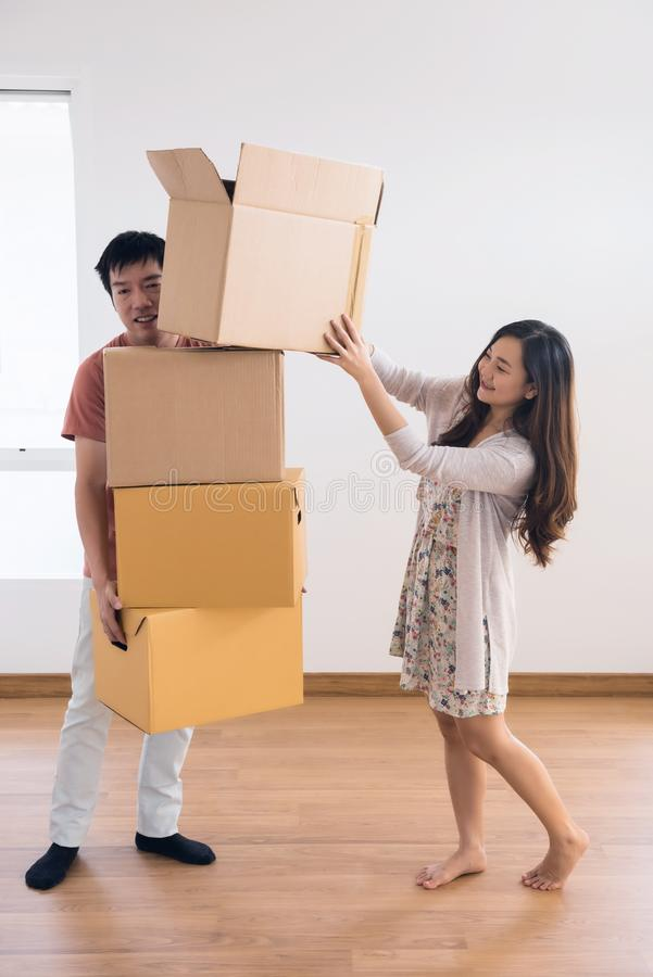 Asian handsome exhausted husband man carrying many stacked cardboard boxes royalty free stock photography